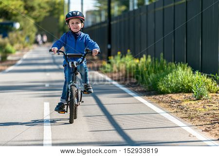 Happy aussie boy riding his bicycle on bike lane on a day South Australia