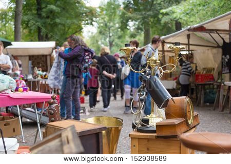 Market boot with objects beeing selled at the weekend flea market in Berlin city center. Out of focus curious visitors in the background.