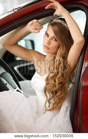 Young sensual bride sits in the red car.Selective focus.
