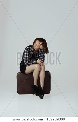 Photo with girl sitting on suitcase and waiting for somebody
