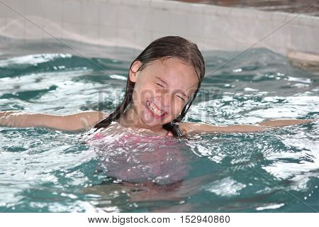 Girl child frolicking in the shallow end of a swimming pool.
