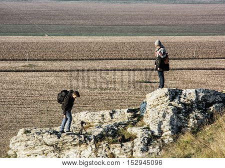 Young caucasian woman with teenage son on the Drazovce peak. Hiking theme. Autumn fashion. People rocks and seasonal fields.