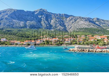 Croatian coastline with mountains and yacht on a sunny summer day. Popular Europe summer destination