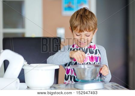 Cute funny blond kid boy baking apple cake in domestic kitchen. Child having fun with helping and working with mixer, flour, eggs and fruits.
