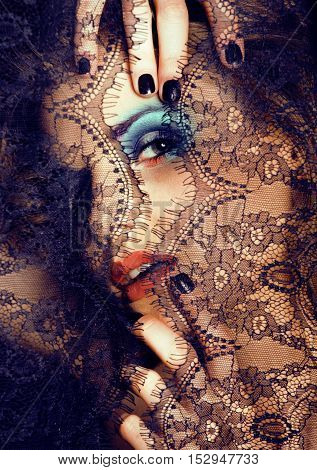 portrait of beauty young woman through lace close up mistery bright makeup