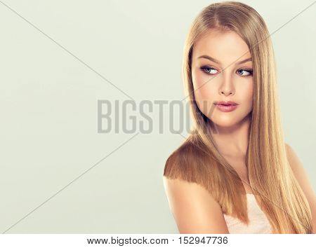 Beautiful blonde girl  model with long straight smooth hair . A woman with healthy straight hairstyle