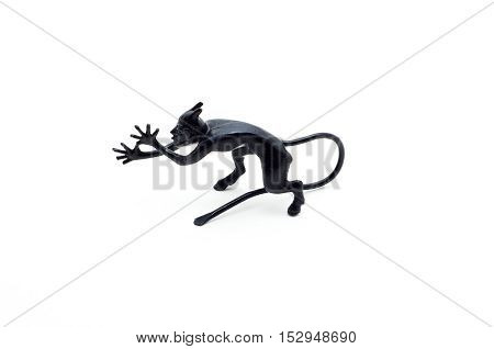 Metal devil figurine in a sneering posture isolated on white background.