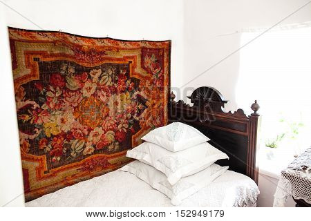 Old russian interior. Russian interior. Bed in the room. White interior. rural interior. Rural interior of a bedroom. Russian bedroom. Rural tenor of life.