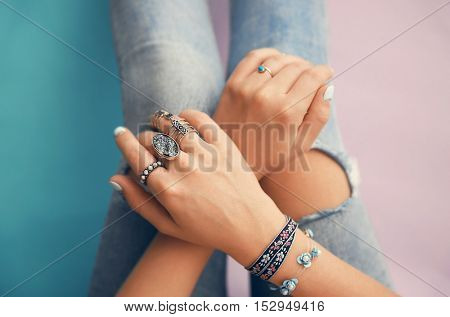 Female hands with jewelry on color background