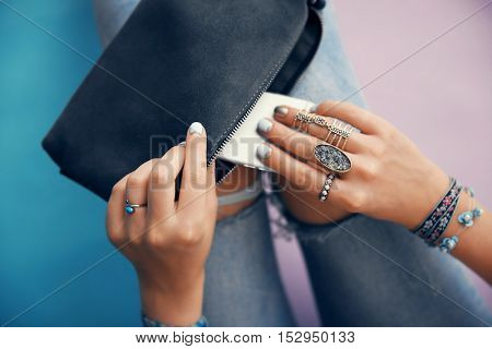 Female hands with jewelry, cellphone and clutch bag on color background