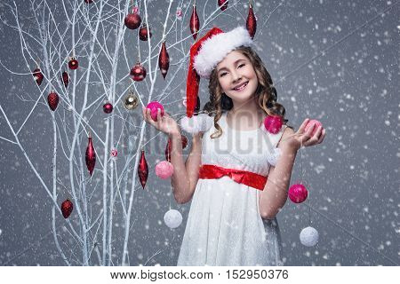 Beautiful teen girl with long curly hair in white dress with red ribbon belt and santa cap on head standing near white tree branches wiht christmas decorations and holding pink garland. Studio shot on grey background. Copy space.