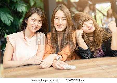 Three beautiful happy Asian girls smile and laugh together. Image with sunlight filter.
