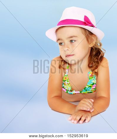 Gentle little tanned girl and hat. The girl averted her eyes towards the camera.On the background of summer blue sky and fluffy clouds.
