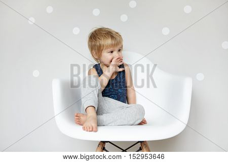 Cute Little Blonde Barefooted Preschool Boy In Sleeping Suit Looking Suprised And Amazed, Covering H