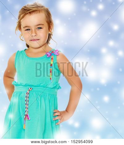 Fashionable little tanned girl in a smart blue dress. She looks straight into the camera. Close-up.Blue Christmas festive background with white snowflakes.