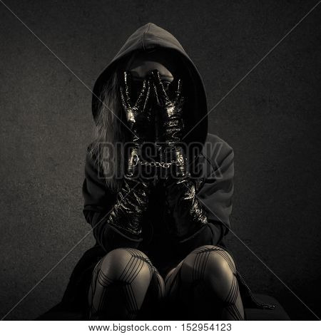 Low key special toned photo. Portrait of young woman dressed in hooded cloak holding hands in black leather gloves in cluffs chained together in front of face