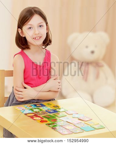 Intelligent little girl demonstrates how she folded cards with drawings on the table.In the children's room in which sits a Teddy bear.