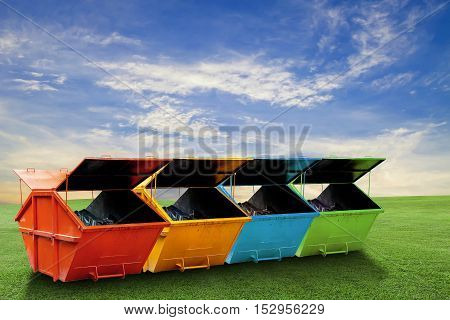 Colorful Industrial Waste Bin (dumpster) for municipal waste or industrial waste on green grass and blue sky background, ecology concept
