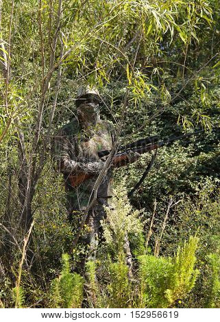 Camouflaged hunter in jungle like area with sniper rifle He must blend into surrounding to not be detected