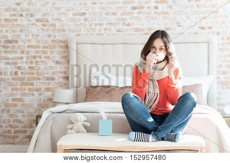 Winter epidemics. Nice moody young woman sitting in a bedroom and wearing a scarf while suffering from cold