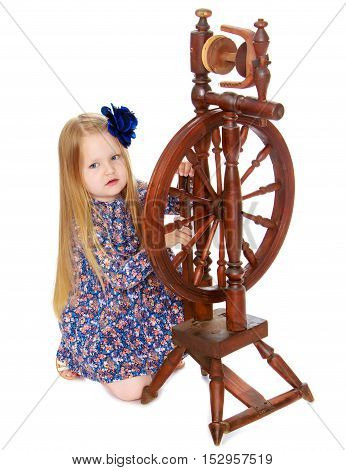 Curious little girl with long blond hair below the shoulders, which are attached to a large blue flower . The girl enthusiastically looking at the old spinning wheel - Isolated on white background