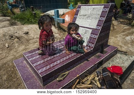 Chichicastenango Guatemala - April 24 2014: Children sitting in a grave in the cemetery of the town of Chichicastenango in Guatemala