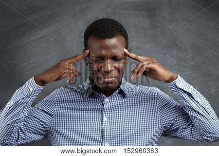 Portrait Of Dark-skinned Entrepreneur Having Bad Headache, Pressing Fingers Against His Temples, Clo