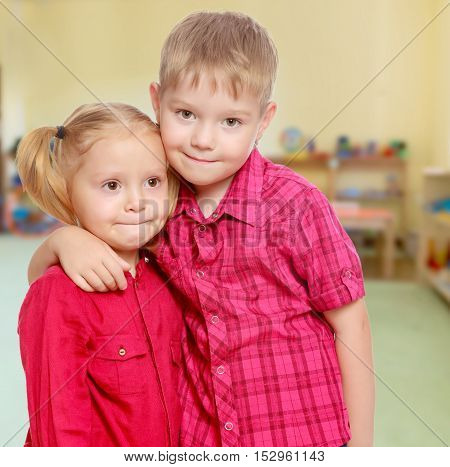 The concept of pre-school education of the child among their peers . on the background of the playroom with shelves for toys. Montessori.Little brother and sister cute hug.