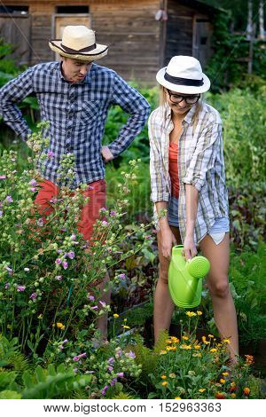 Young gardeners man and woman in garden. She watering flowers, he oversees the process