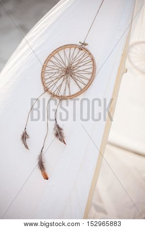 Indian tent. Dreamcatcher on white tent. Hunter of dreams. White tent. Dreamcatcher clouse up.