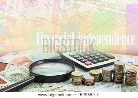 Calculator with coin and Magnifying glass on money banknotes Euro and Dollarswith Written word financial independence