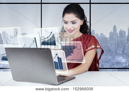 Beautiful Indian businesswoman working in the office with virtual financial graph on the laptop