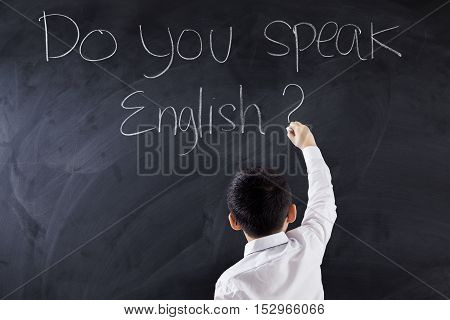 Male primary school student writes text of Do You Speak English on the blackboard