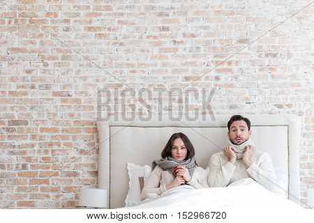 Unpleasant time. Sad unhappy depressed couple lying under the blanket together and looking in front of them while having the influenza