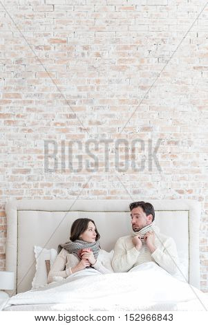 Having a bed rest. Nice cheerless young couple lying on the bed and looking at each other while having a cold