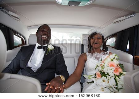 Beautiful Young Couple Smiling Happily On Wedding-day, Sitting In Limousine.