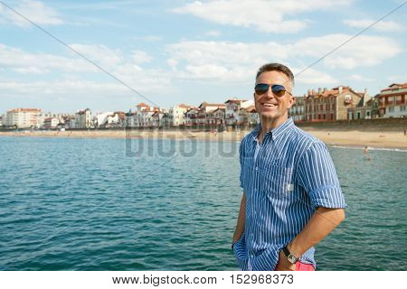 Handsome cheerful smiling man. Outdoor male portrait. Middle-aged man resting at seafront, summer outdoor portrait, image toned.