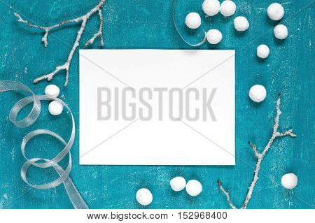 Painted blue aged background with branches, ribbon and white balls