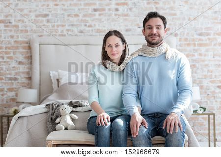 Happy together. Pleasant happy young couple sitting side by side and sharing a scarf while looking at you