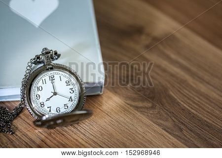 Luxury Pocket Watch Over The Book On The Wooden Table With Copy Space