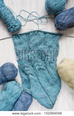 Knitted blue scarf and skeins of wool on the wooden table