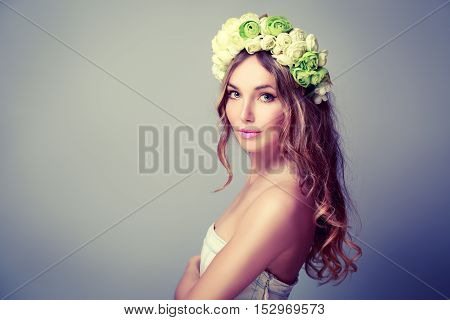Portrait of a Young Woman with Wreath of Roses on Gray Background. Girl with Flowers on Head. Bridal Fashion Crown. Natural Female Beauty Concept. Toned Photo with Copy Space.