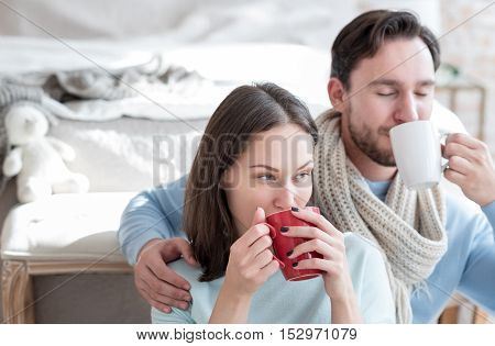 Our favourite drink. Pleasant attractive pensive woman holding a red cup and sipping tea while spending time with her boyfriend