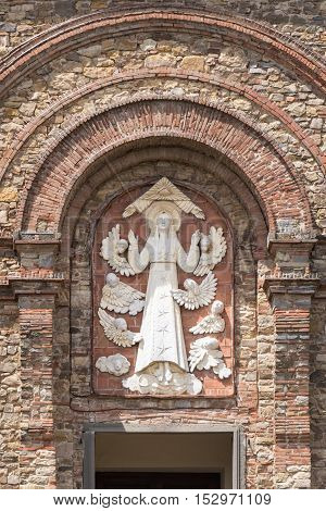 Relief on the facade of the church of the Ascension of Virgin Mary in Panzano in Chianti, Italy