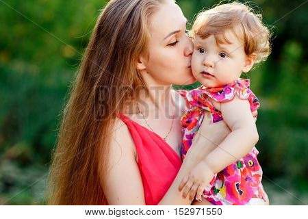 Young mother kissing baby daughter in green park