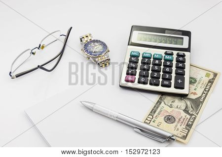 White office desk table with pen calculator glasses and banknote Business Finance background concept