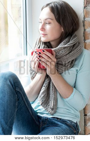 Looking through the window. Peaceful beautiful happy woman holding a tea cup and looking through the window while sitting on a windowsill