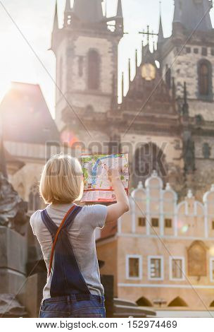 PRAGUE, CZECH REPUBLIC - JUNE 05, 2016: Woman looks at map in the old town square. Travel guide, tourism in Europe, female tourist with map. Kostel Panny Marie pred Tynem. Church of the Virgin Mary.