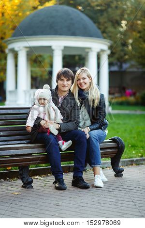 Young parents with daughter sitting on bench against backdrop of mirador in park