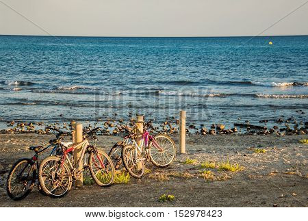 Seascape in last rays of setting sun with bikes parked on the beach. Healthy lifestyle concept. Horizontal.